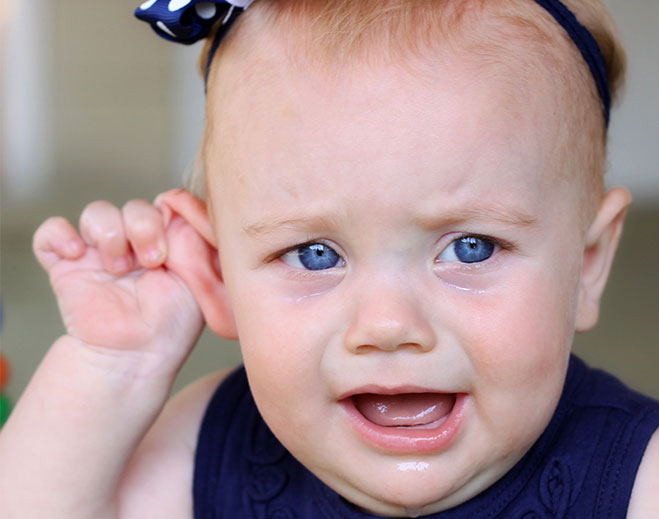 baby holding ear while crying